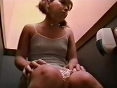 Young oriental amateur babe fingering her clit in public water closet